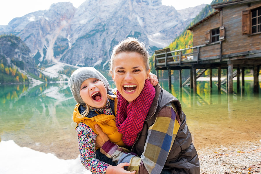 Personal Insurance - Mom and Daughter Laughing with Beautiful Mountains, Lake and Cabin in the Background