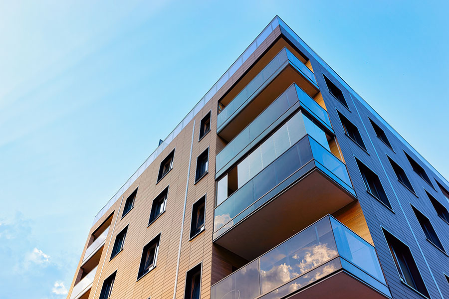 Specialized Business Insurance - Modern Angled Apartment Building with Blue Sky