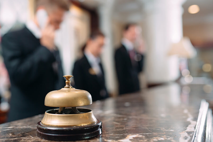Hospitality-Insurance-Front-Desk-Associate-on-the-Phone-with-a-Bell-on-the-Desk-of-a-Luxury-Hotel